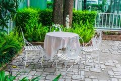 Uppsättning för engelskaträdgårdtabell med vit stålstol i den utomhus- trädgården Royaltyfria Foton