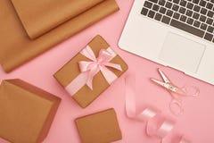 Uppsättning för gåvainpackning med silverbärbara datorn på rosa flatlay Royaltyfri Fotografi