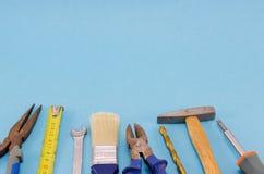 Uppsättning för hjälpmedel för handarbete på blå bakgrund Arkivfoto