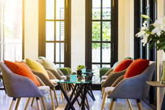 Uppsättning för kaffetabell och moderna stolar med färgrika kuddar Arkivfoton