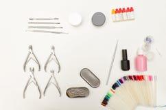 Uppsättning för manicure Hjälpmedel pojkar, spikar polermedel, beläggningen, tofsen och paletten Vit bakgrund, bästa sikt Royaltyfri Foto