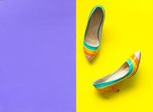Uppsättning för modekvinnatillbehör Moderiktig modecolorfull skor häl oj lila- och gulingbakgrunden Royaltyfri Fotografi