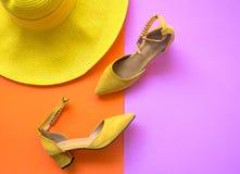 Uppsättning för modekvinnatillbehör Moderiktig modeguling skor häl, stilfull stor hatt Colorfull apelsin och rosa färgbakgrund Arkivbild