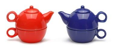 Uppsättningar av blåa och röda keramiska tekannor och rånar Royaltyfri Foto