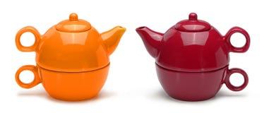 Uppsättningar av orange och röda keramiska tekannor och rånar Royaltyfri Bild