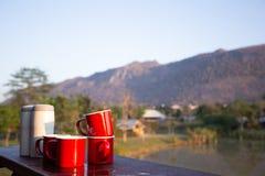 Uppsättningar av röda exponeringsglas av den varma drinken med varma torktumlare på en tabell med bergsikt Arkivfoto