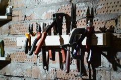 Uppsättningen av den olika mannen bearbetar utsikt på tegelstenväggen av garaget, seminarium Plattång skärare, en skruvstäd, sax, royaltyfri fotografi