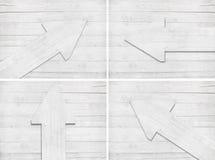 Uppsättningen av den vit skrapade träpilen är på väggen Arkivfoto