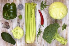Uppsättningen av grönsaker på vit målade träbakgrund arkivfoto