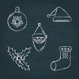 Uppsättningen av julsymboler skissar på den svart tavlan Arkivfoton