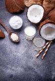 Uppsättningen av kokosnöten mjölkar, bevattnar, olja och shavings royaltyfri bild