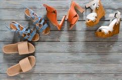 Uppsättningen av kvinnors skokilar, häl och plana sandaler på grå färger uppvaktar Arkivbilder