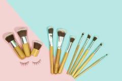 Uppsättningen av makeup borstar på komponerade rosa färger och aqua som färgas royaltyfria bilder