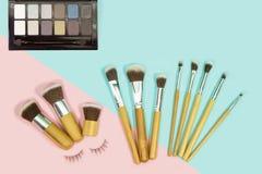 Uppsättningen av makeup borstar på komponerade rosa färger och aqua som färgas royaltyfri bild