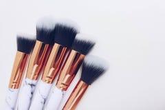 Uppsättningen av makeup borstar på vit färgad komponerad bakgrund arkivbilder
