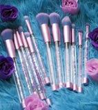 Uppsättningen av makeupborstar med mousserar på rosa färger, lila och blått färgad komponerad bakgrund arkivfoto