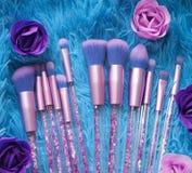 Uppsättningen av makeupborstar med mousserar på rosa färger, lila och blått färgad komponerad bakgrund Royaltyfria Foton