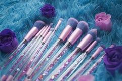 Uppsättningen av makeupborstar med mousserar på rosa färger, lila och blått färgad komponerad bakgrund Royaltyfri Foto