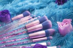 Uppsättningen av makeupborstar med mousserar på rosa färger, lila och blått färgad komponerad bakgrund Royaltyfri Bild
