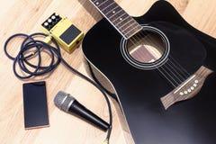 Uppsättningen av musik anmärker med den svarta accoustic gitarren, mikrofonen, mobil musik Arkivfoton