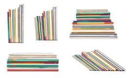 uppsättningen av olik olik colorfull bokar i bunten som isoleras på vit bakgrund Arkivfoto