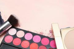 Uppsättningen av olika makeupprodukter i rosa färger tonar Arkivfoton