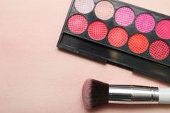 Uppsättningen av olika makeupprodukter i rosa färger tonar Fotografering för Bildbyråer