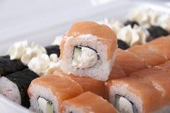 Uppsättningen av sushi från svart och guling rullar Arkivfoto