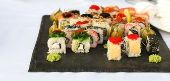 Uppsättningen av sushirullar med vasabi och ingefäran på ett mörker kritiserar plattan royaltyfria bilder