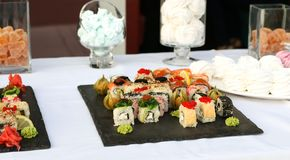 Uppsättningen av sushirullar med vasabi och ingefäran på ett mörker kritiserar plattan arkivfoto