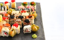 Uppsättningen av sushirullar med vasabi och ingefäran på ett mörker kritiserar plattan Arkivfoton