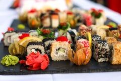 Uppsättningen av sushirullar med vasabi och ingefäran på ett mörker kritiserar plattan Royaltyfri Bild