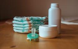 Uppsättningen av tillbehör för behandla som ett barn disponibla blöjor, saker för barnavård Arkivfoto