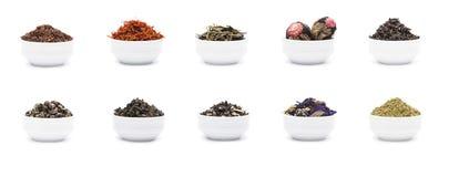 Uppsättningen av torra teblad i vitt porslin bowlar arkivbild