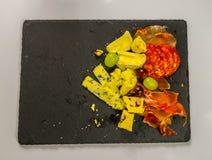 Uppsättningen av tre spanska skinkor och en uppsättning av franska ostar Arkivfoton