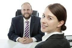 Uppsöka kvinnan för brunetten för affärsmannen på att le för skrivbord royaltyfri fotografi