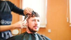 Uppsökt i frisersalong - frisören flyttar sig omkring och gör män frisyr, tidschackningsperiod stock video