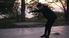 Uppsökt man i svart sportssuit som gör sträcka övningar utomhus för tillbaka muscules genom att använda motståndsmusikbandet utom arkivfilmer
