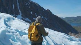 Upps?kt man med en gul ryggs?ck och en turist- ?versikt i hans h?nder, mot bakgrunden av vinterlandskapet stock video