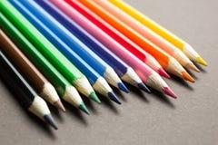 Upps?ttning av kul?ra blyertspennor p? en gr? bakgrund royaltyfria foton