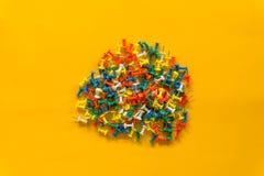 Upps?ttning av pushben i olika f?rger h?ftstift Top besk?dar P? gul bakgrund royaltyfria foton