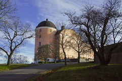 Uppsala 16th century castle in autumn. Autumn by the castle of Uppsala, Sweden. Cloudy sky and trees contrasts the apricot walls of this beautiful historic stock photos