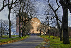 Uppsala 16th century castle in autumn. Autumn by the castle of Uppsala, Sweden. Cloudy sky and trees contrasts the apricot walls of this beautiful historic royalty free stock images