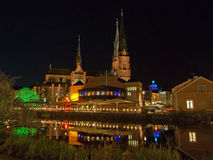 Uppsala, west side of Fyris river by night. A scenic view of the west side of Fyris river by night with Uppsala Cathedral behind a market hall with its popular stock photography