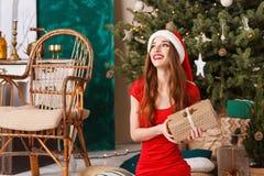 Uppsluppen julkvinna som bär den Santa Hat Sitting And Holding A gåvan arkivbilder