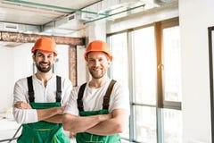 Uppsluppna le konstruktörer som viker händer arkivfoton
