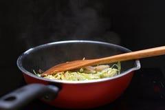 Uppståndelse Fried Mixed Vegetable i källa för teflonpannavärme vid inductio arkivbilder