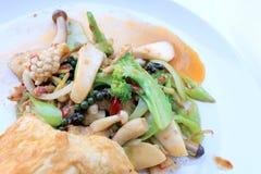 Uppståndelse stekte kryddig skaldjur med svartpeppar och thai stilomelett med ris på den vita maträtten, thailändsk kryddig örtma royaltyfri foto