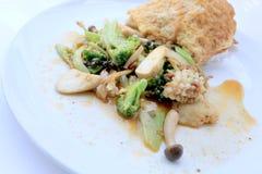 Uppståndelse stekte kryddig skaldjur med svartpeppar och thai stilomelett med ris på den vita maträtten, thailändsk kryddig örtma arkivbilder