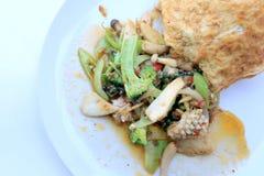 Uppståndelse stekte kryddig skaldjur med svartpeppar och thai stilomelett med ris på den vita maträtten, thailändsk kryddig örtma royaltyfria bilder